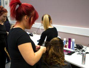 Opiskelija laittaa asiakkaan hiuksia Salpauksen Kauneustalossa