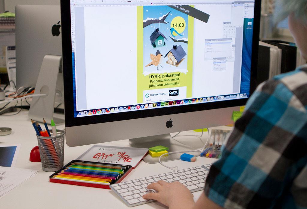 Tietokoneen näyttö ja värikyniä pöydällä