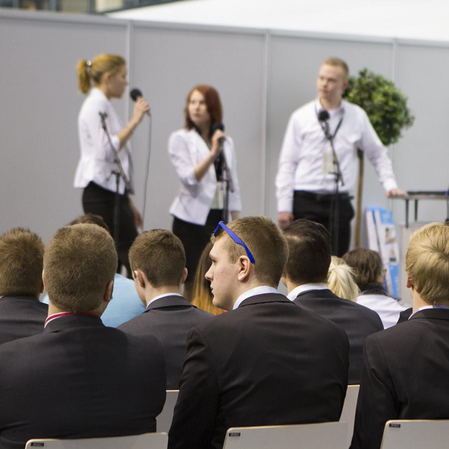 Juhlatilaisuudessa yleisöä sekä esiintyjiä mikrofonit kädessä.