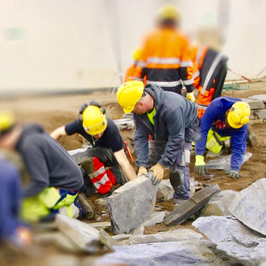 Kivirakentajat asettelevat kiviä pihalle.