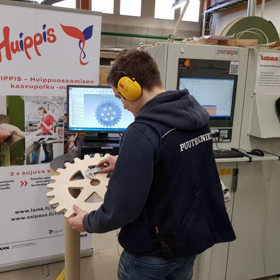 Puuseppäopiskelija työkalun kanssa mittaamassa.