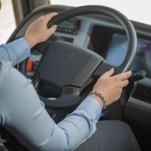 Kädet auton ratissa