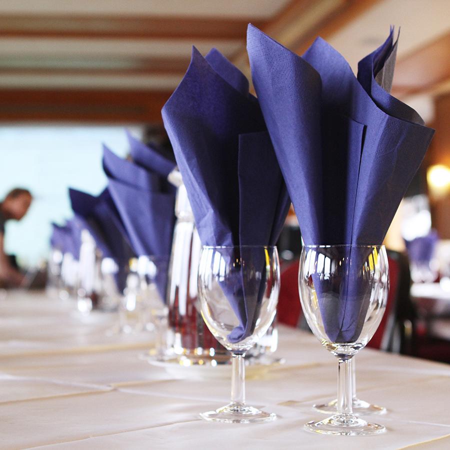 Pöydällä jalallisia laseja sinisillä serveteillä.