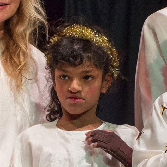 Tyttö enkelikuoron esityksessä.