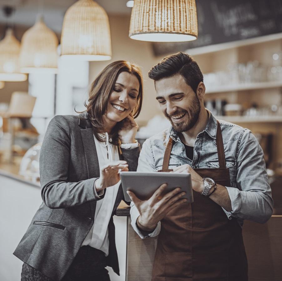 Mies ja nainen myymälätiskin edessä katsovat pädiä
