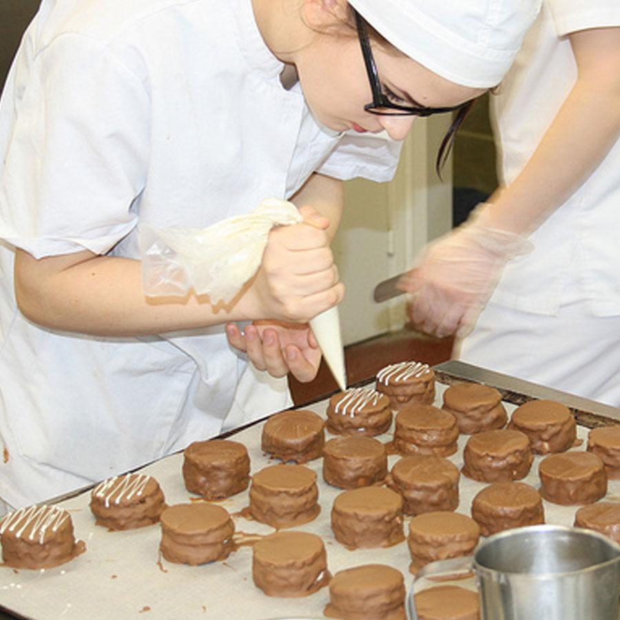 Leipuri-kondiittori koristelemassa leivonnaisia.