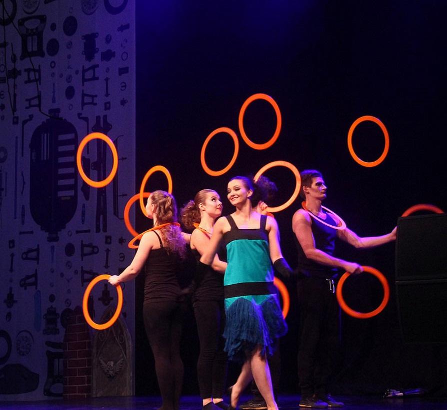 Sirkusalan opiskelijat heittävät oransseja renkaita esityksessä.