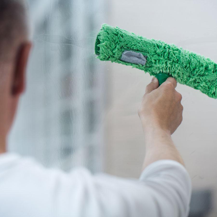 Kodinhuoltajaopiskelija pesee ikkunaa lastalla.