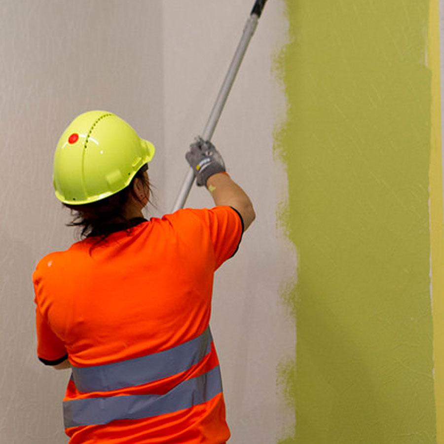 Maalariopiskelija maalaa seinää.
