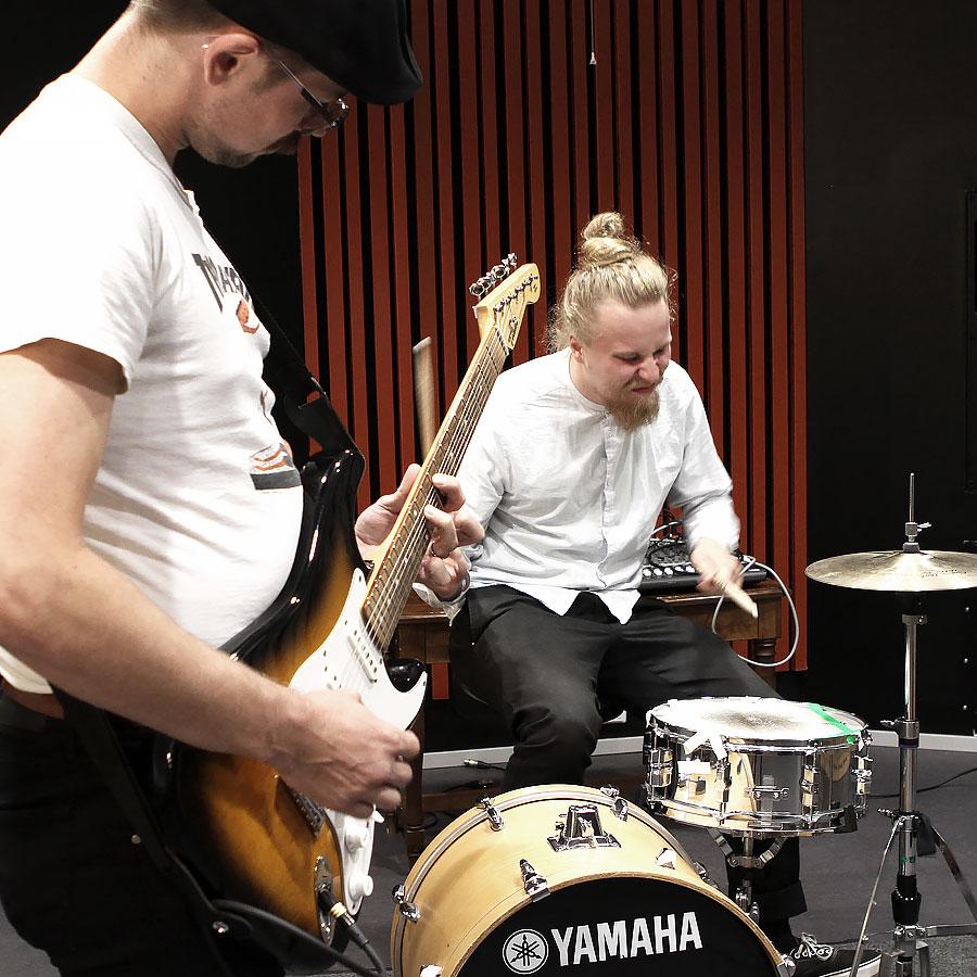 Musiikkiteknologian opiskelijat soittavat kitaraa ja rumpuja.