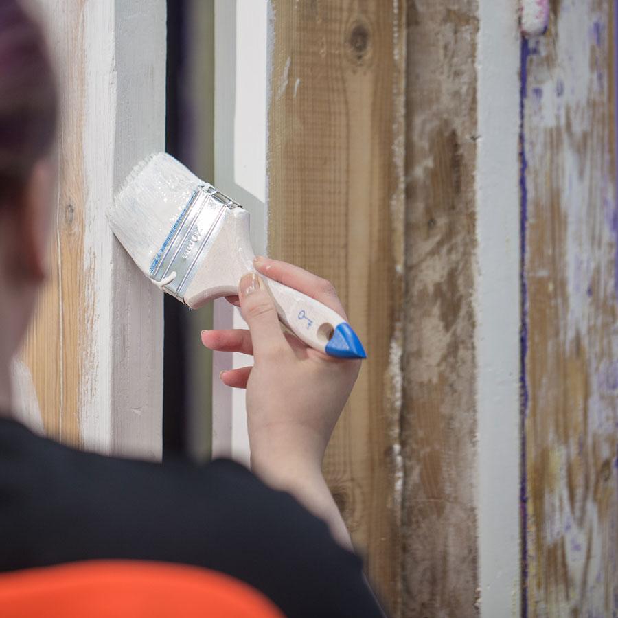 Pintakäsittelijäopiskelija maalaa puuseinää.