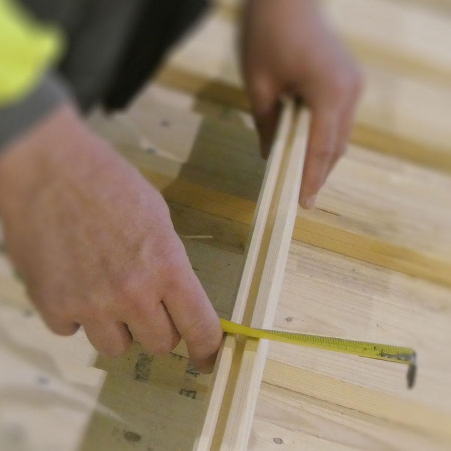Talonrakentajaopiskelija mittaa puurimaa.
