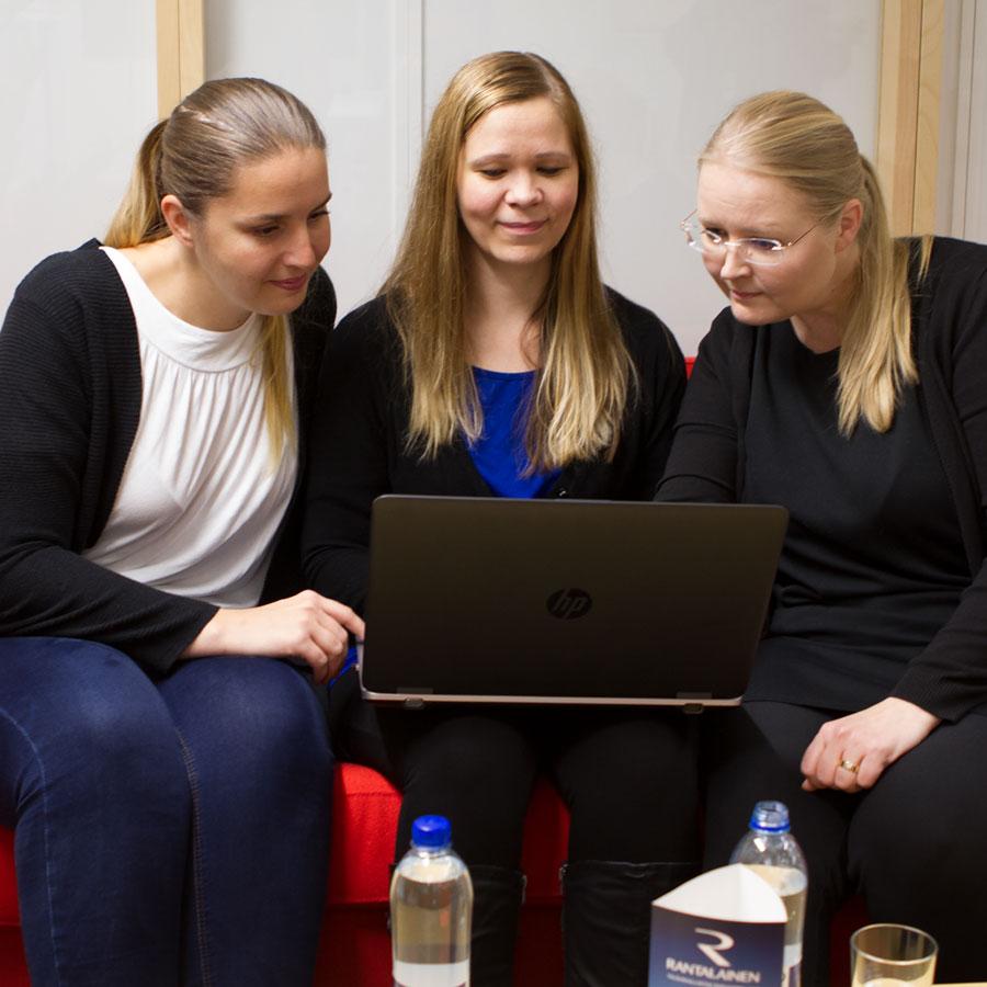 Tuotekehitystyön erikoisammattitutkinnon opiskelijat katsovat kannettavaa tietokonetta.