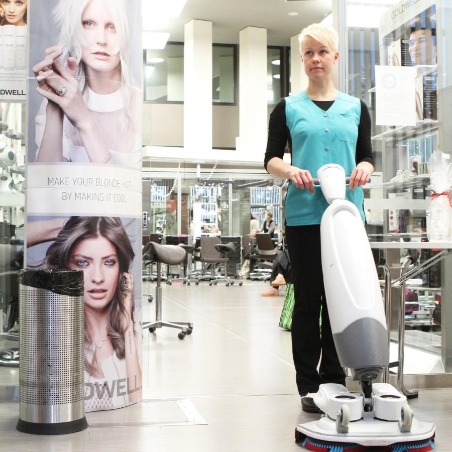nainen siivoaa siivouskoneella lattiaa