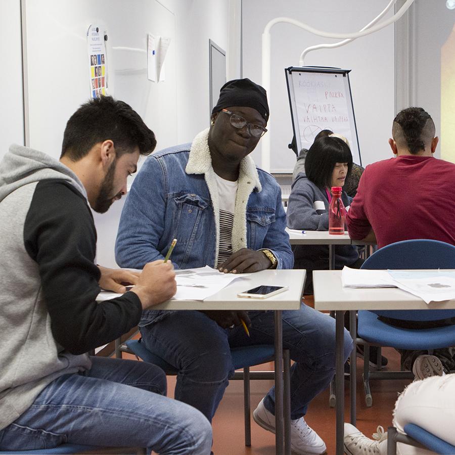 Maahanmuuttajaopiskelijoita opiskelemassa.