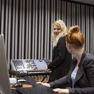 musiikkiopiskelijat musiikkilaitteiden luona