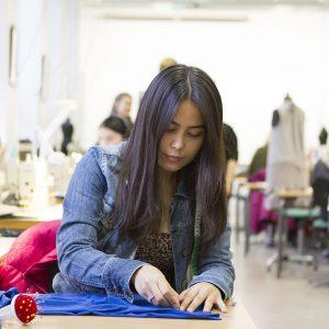 Vaatetusalan opiskelija mittaa kangasta