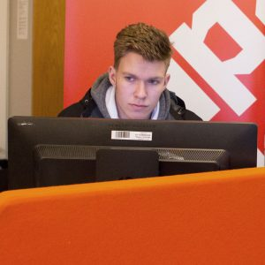 Datanomiopiskelija tietokoneen ääressä.