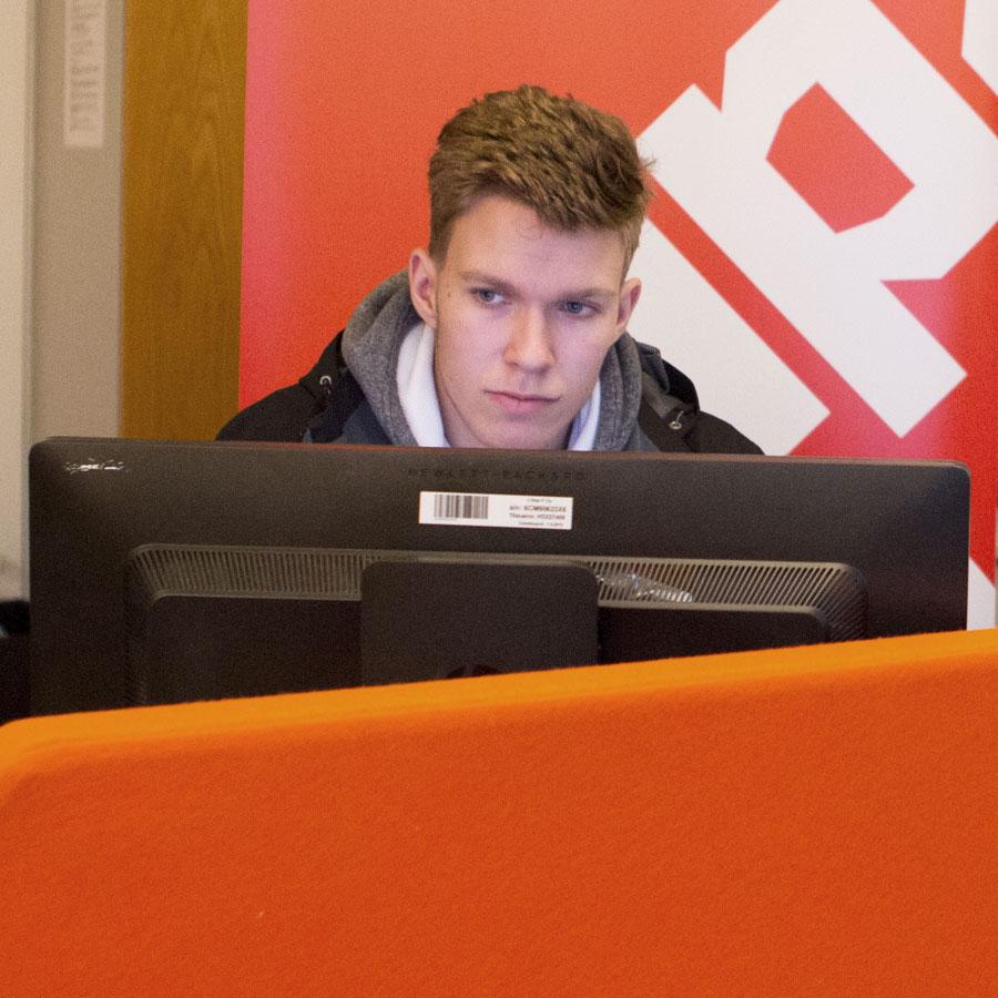 Opiskelija tietokoneen ääressä.