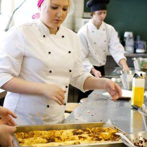 Hygieniaosaamiskoulutusopiskelijat laittavat ruokaa.