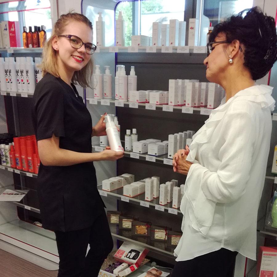 Kosmetiikkaneuvoja esittelee asiakkaalle tuotteita.