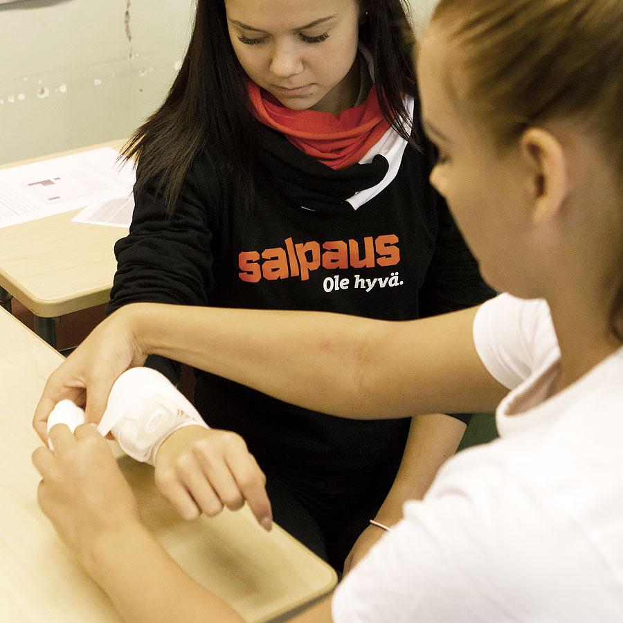 Lähihoitajaopiskelijat opettelevat haavan sitomista.