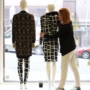 Markkinointiviestinnän opiskelija pukee mallinukkea.