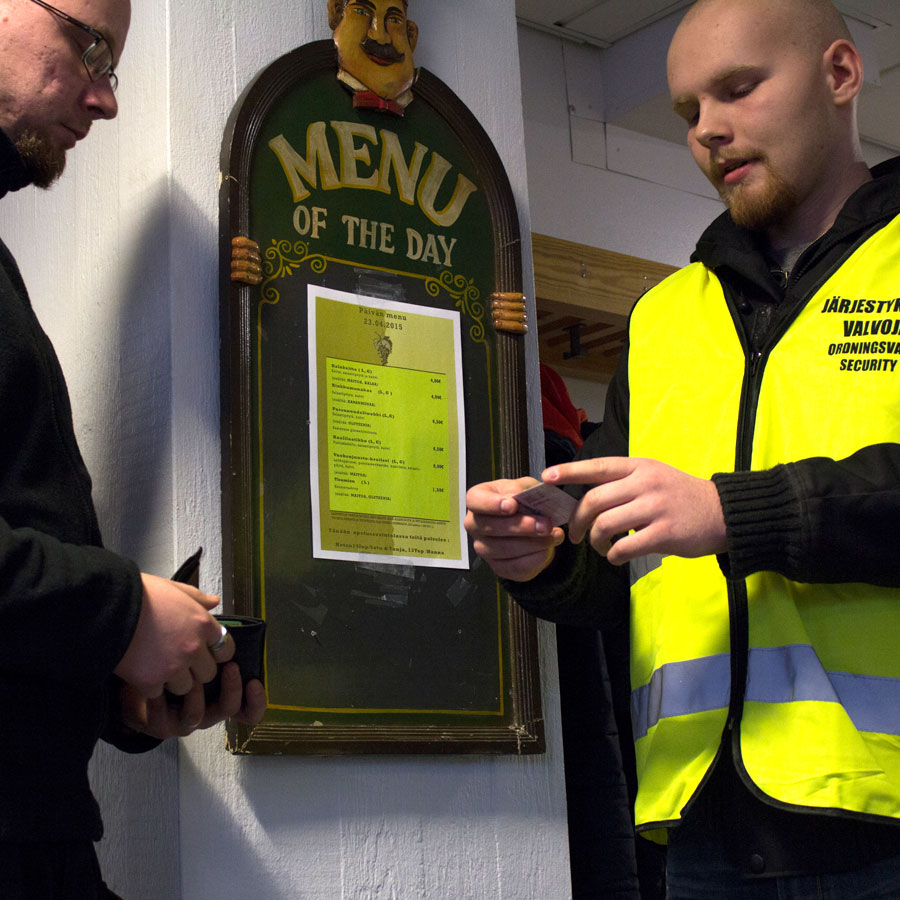 Turvallisuusvalvojaopiskelija ravintolan ovella.