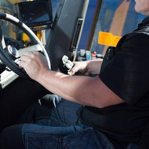 Yhdistelmäajoneuvonkuljettajan ammattitutkinnon suorittaja auton ratissa.