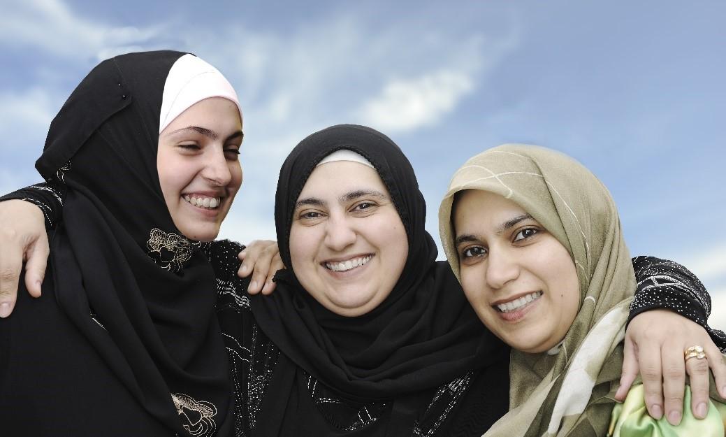 Kolme maahanmuuttajanaista pitävät käsiä toistensa hartioilla hymyillen.