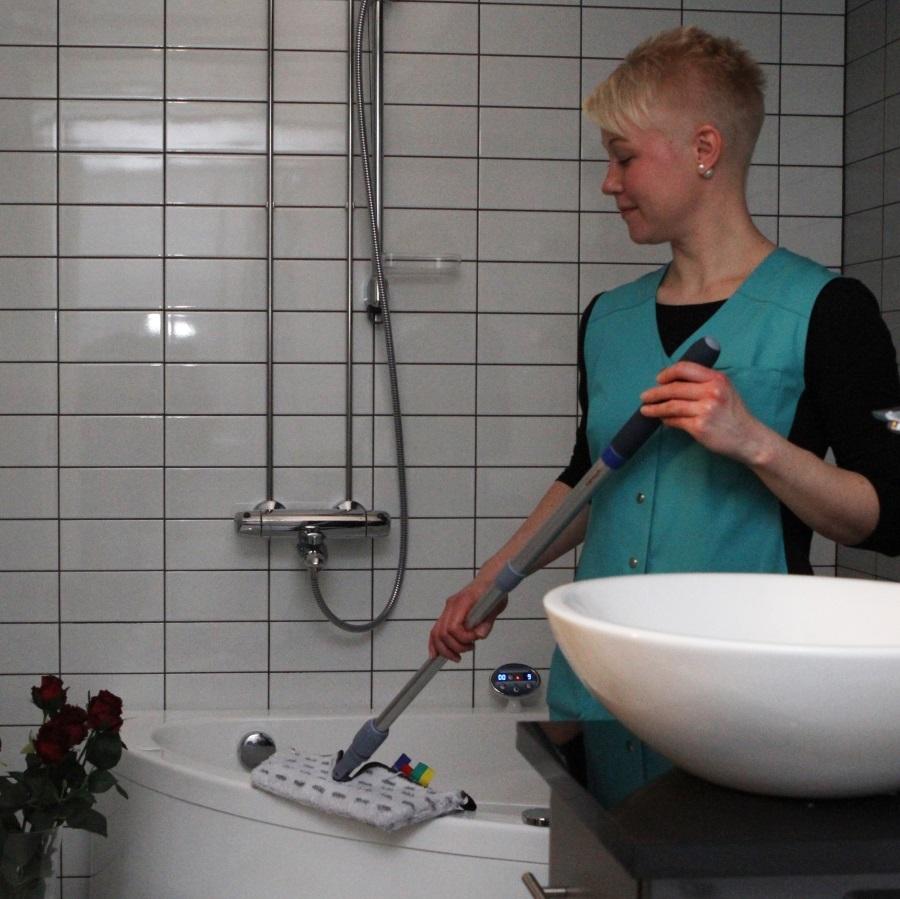 Nainen siivoamassa kylpyhuonetta.
