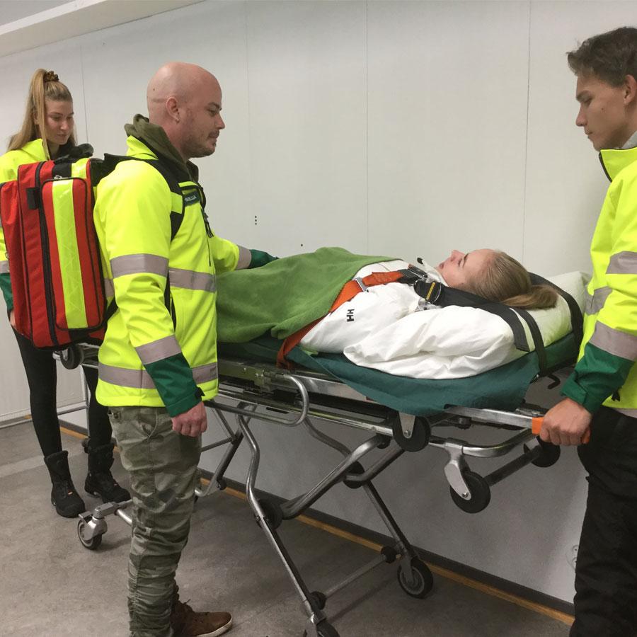 Perustason ensihoidon opiskelijat valmistelevat potilasta turvalliseen kuljetukseen.