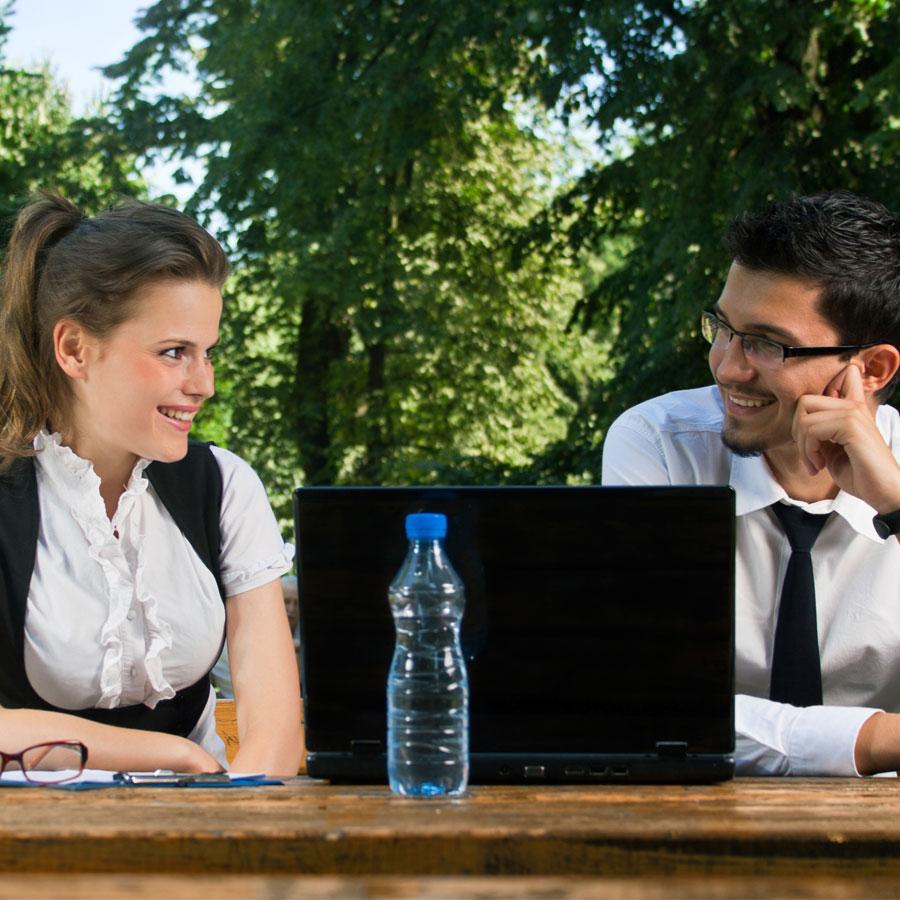Kaksi henkilöä opiskelemassa ulkona pöydän ääressä.
