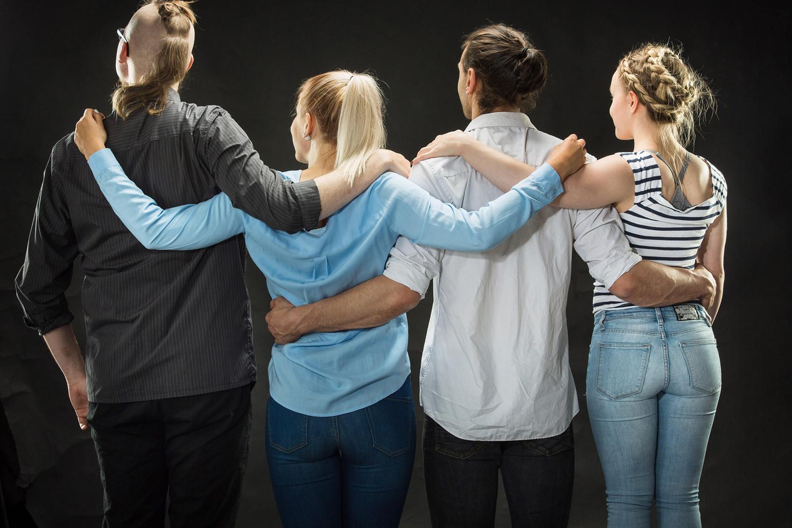 Neljä opiskelijaa kädet toistensa hartioilla. takaapäin kuvattuna.
