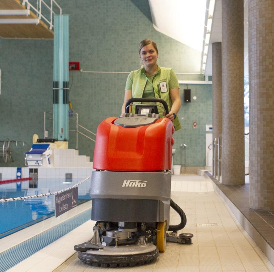 Nainen käyttää siivouskonetta uimahallissa.