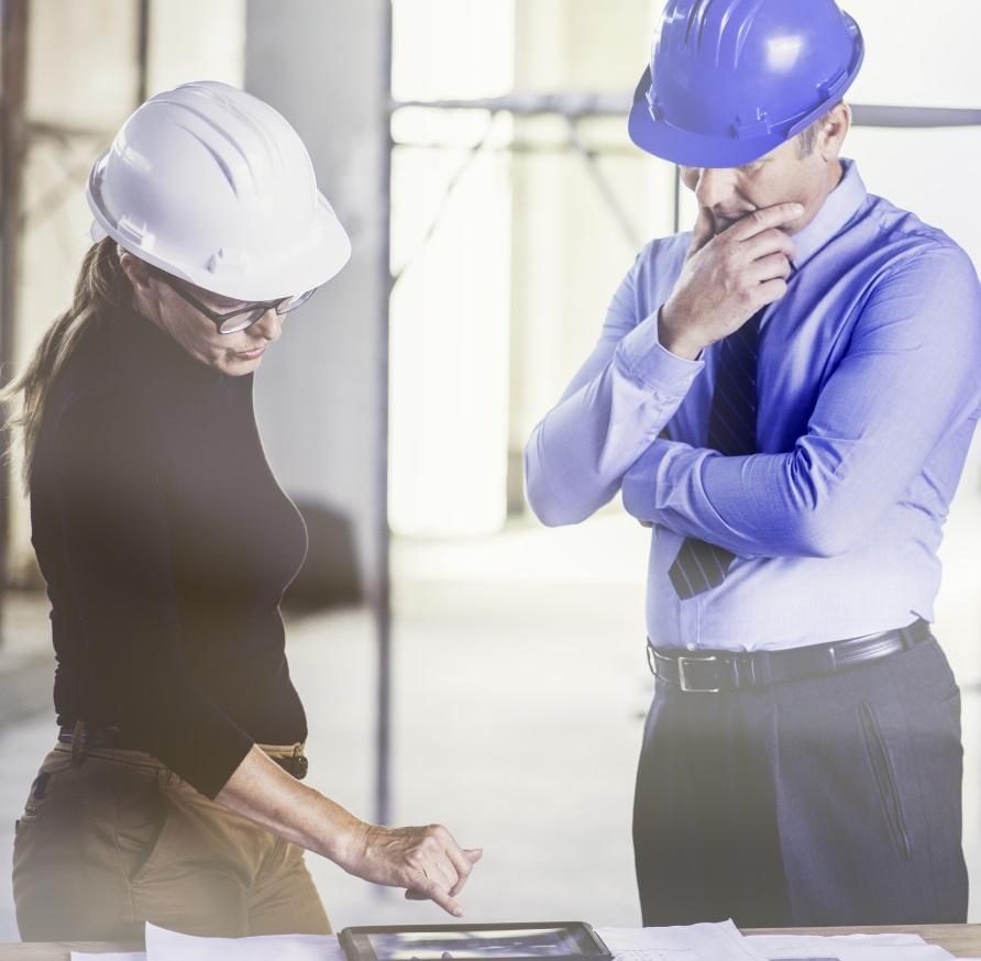 Kuvassa kaksi teollisuuden esimiestä keskustelevat pöydän ääressä pädin tai tietokoneen edessä.