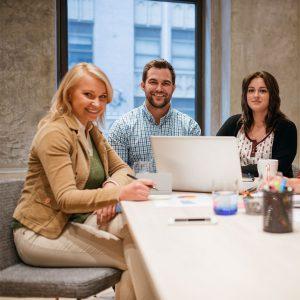 Kaksi naista ja mies istuvat pöydän ääressä kokouksessa.