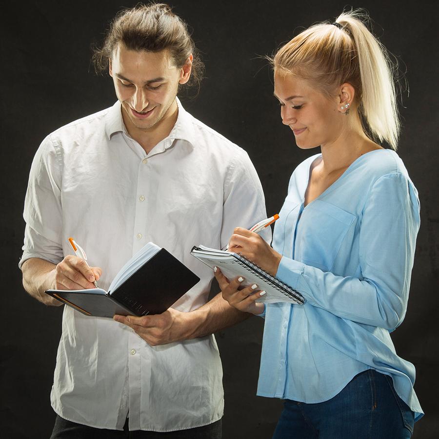 Kaksi opiskelijaa täyttämässä muistivihkojaan.