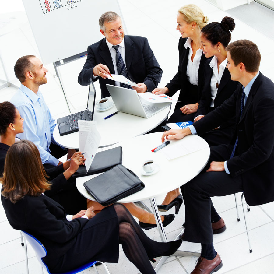 Henkilöitä pöydän ympärillä kokouksessa.