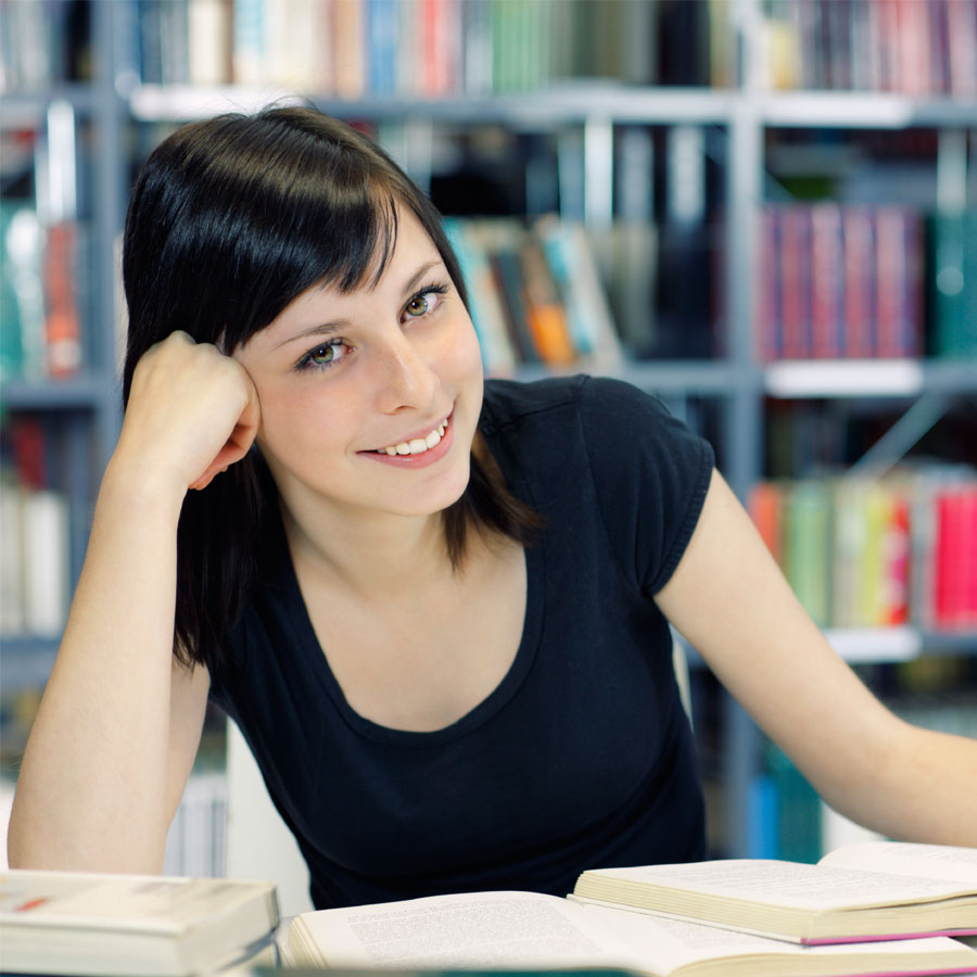 Opiskelija kirjojen äärellä.