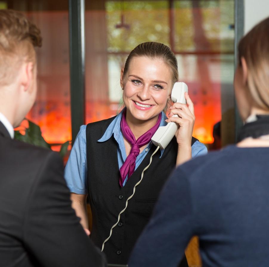 Vastaanottovirkailija vastaa puhelimeen ja palvelee tiskillä olevia asiakkaita.