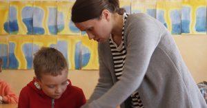 Maria auttaa oppilasta