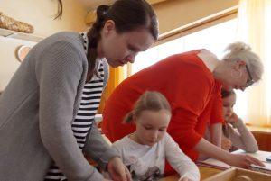 Maria auttaa opettajaa ohjaamalla oppilaita käsityötunnilla.