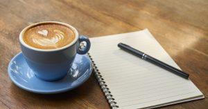 Kahvikuppi, lehtiö ja kynä pöydällä