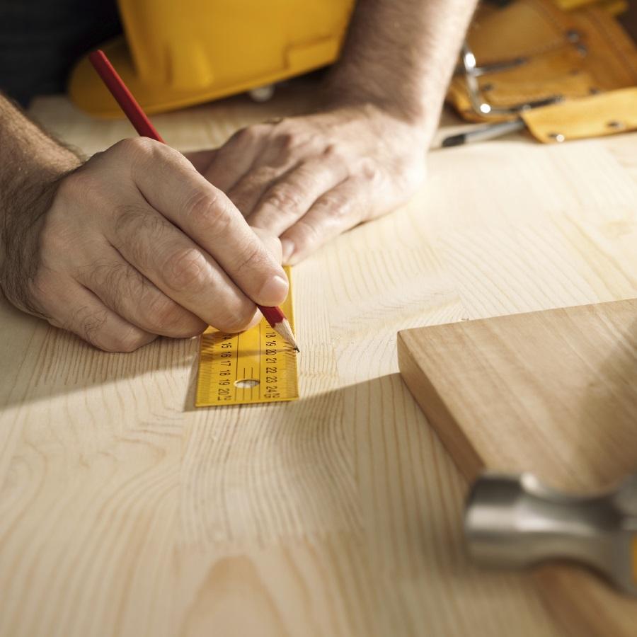 Henkilö mittaa puutavaraa.
