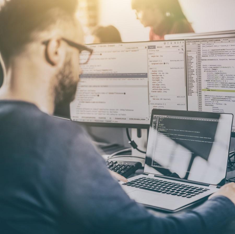 Mieshenkilö tietokoneen ja useiden näyttöjen edessä.