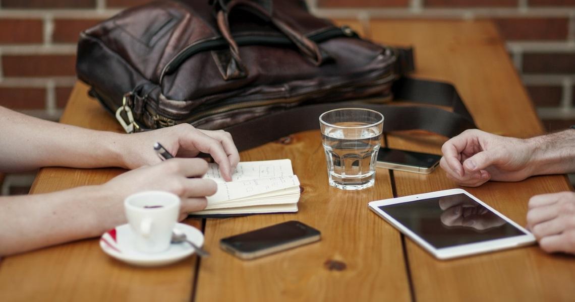 Kahvilapöydällä puhelimia ja kahvikuppi