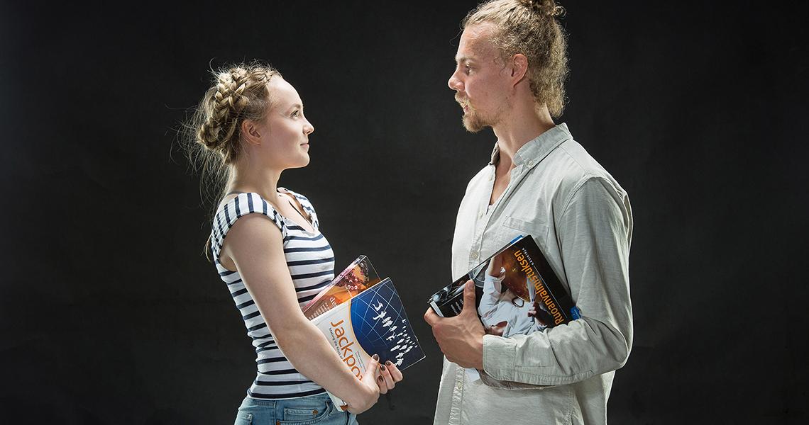 Kaksi opiskelijaa kirjojen kanssa katsoo toisiinsa