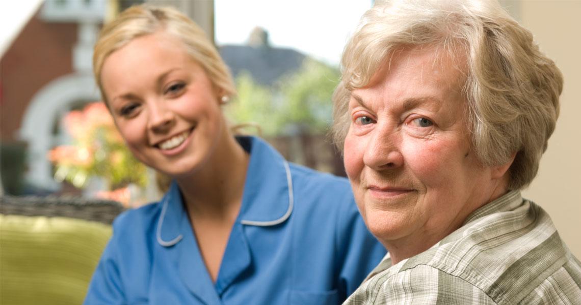Lähimmäistyö, lähihoitaja ja ikäihminen istuvat vierekkäin.