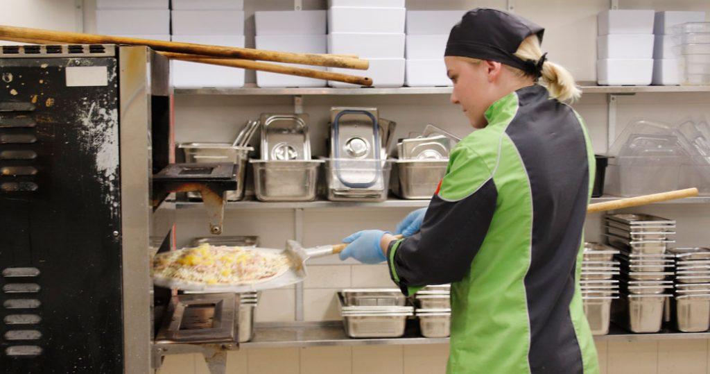 Alina nostaa pizzaa uuniin